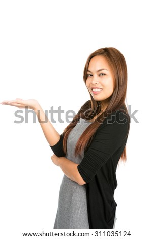 Side profile of gorgeous Asian woman wearing gray dress, black sweater looking at camera holding hand flat out displaying imaginary inserted product on open palm. Thai national of Chinese origin Half - stock photo