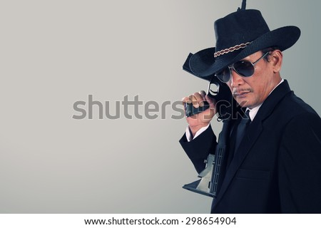 Side profile of old gangster holding a gun, over gray background for copy space - stock photo
