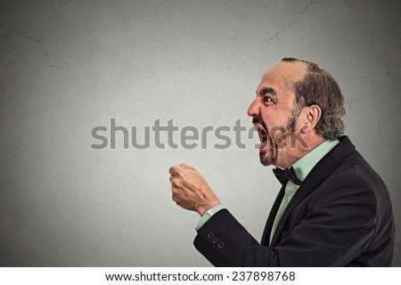Side profile portrait bitter mad displeased pissed off angry grumpy corporate man open mouth fist in air, screaming, yelling isolated grey background. Negative human emotion facial expression feeling - stock photo