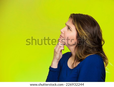 Side profile portrait happy beautiful woman thinking looking up isolated green background with copy space. Human face expressions, emotions, feelings, body language, perception - stock photo