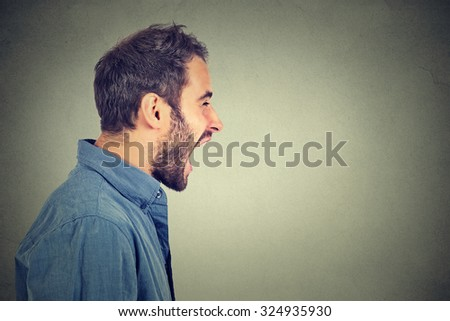 Side profile portrait of young angry man screaming  - stock photo