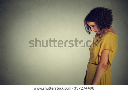 Side profile sad lonely young woman looking down isolated on gray wall background. Human emotion, face expression  - stock photo