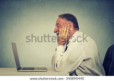 Side profile senior man using laptop computer reading email news watching video. E-learning concept  - stock photo