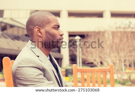 side profile stressed young businessman sitting outside corporate office looking away unhappy. Negative human emotion facial expression feelings. - stock photo