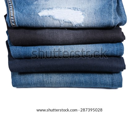 Side Profile View of Different Types of Blue Jeans Folded and Stacked on White Background, Five Denim Jeans of Varying Color Washes and Styles - stock photo