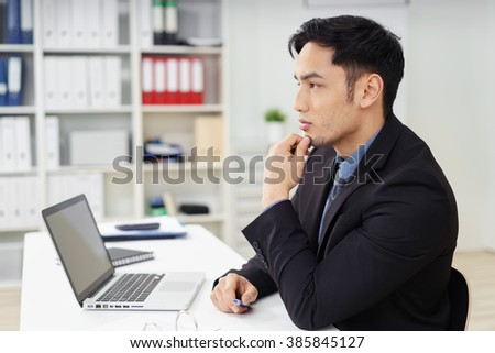 Side profile view of handsome serious young businessman in dark suit in deep thought at desk with open laptop in small office