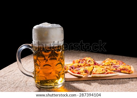 Side Profile View of Mug of Beer with Frothy Head Beside Slices of Pizza Arranged on Wooden Cutting Board on Burlap Covered Table Surface - stock photo