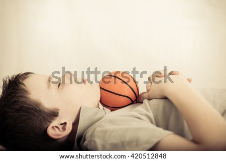 Side profile view on single cute child asleep with little basketball under chin and folded hands on chest - stock photo