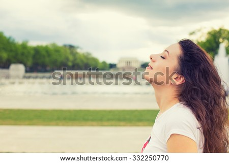 Side profile woman smiling looking up to blue sky, celebrating enjoying freedom. Positive human emotion face expression feeling life perception success, peace of mind concept. Free happy girl