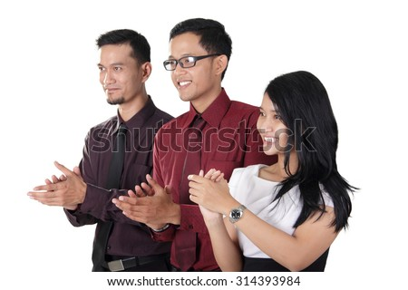 Side profiles of three happy Asian businesspeople clapping hands together, isolated on white background - stock photo