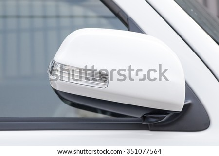 Side rear-view mirror closed for safety at car park - stock photo