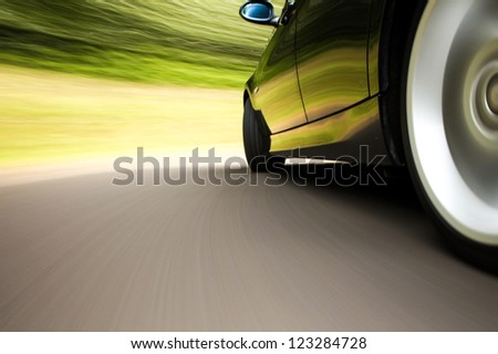 Side rear view of black sport car with heavy blurred motion - stock photo