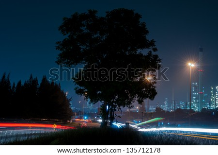Side refinery with car light at dusk - stock photo