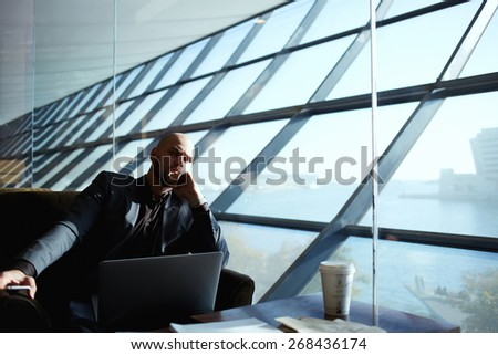 Side shot of handsome successful businessman pensively sitting near the window thinking about the work plan, attractive young business man relaxing in airport hall next to the window, deep in thought - stock photo