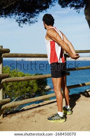 Side shot of handsome young runner stretching his arms before starting his run while standing on edge of a cliff with a wooden fence and enjoying ocean view from altitude - stock photo