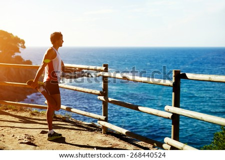 Side shot of handsome young runner stretching his legs before starting his run while standing on edge of a cliff with a wooden fence and enjoying ocean view from altitude, flare sunset light - stock photo