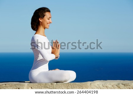 Side shot of smiling beautiful young woman practicing yoga on a sunny day with amazing sea horizon on background, woman seeking enlightenment through meditation, relaxed girl performing yoga routine - stock photo