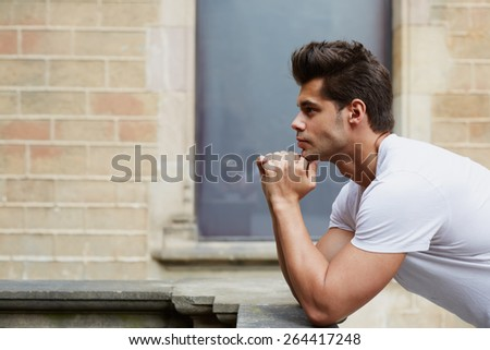 Side shot portrait of handsome man resting chin on clasped hands, confident man thinking about his choice, pensive man standing on brick wall background  - stock photo
