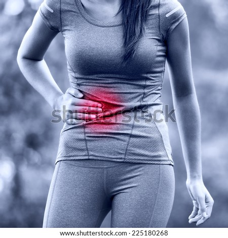 Side stitch - woman runner side cramps after running. Jogging woman with stomac side pain after jogging work out. Female athlete. - stock photo