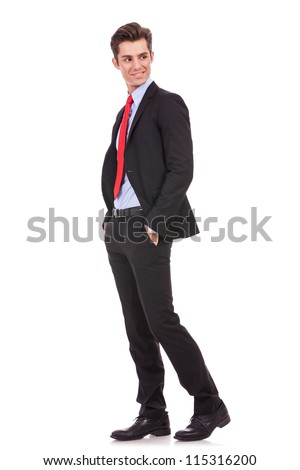 side vie of a young business man standing with his hands in pockets and looking to his back on white background - stock photo