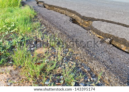Side view asphalt road broken due to collapsing ground until the grass grows. - stock photo