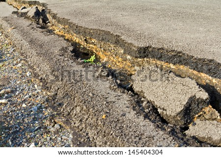 Side view asphalt road broken due to collapsing ground until the grass grows  - stock photo
