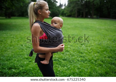 stock photo side view beautiful blonde mom with a ponytail in sportswear holds a child in a gray may sling on 675225340 sling stock images, royalty free images & vectors shutterstock  at gsmx.co