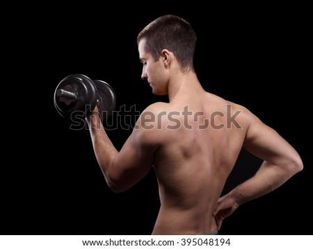side view bodybuilder lifting  black dumbbell, athlete on black background - stock photo