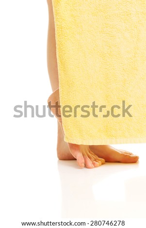 Side view elegant female legs covered with a yellow towel. - stock photo