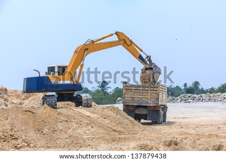 side view excavator loading soil on dumper truck at dolomite mines site - stock photo