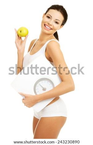 Side view fit woman with an apple and weight. - stock photo