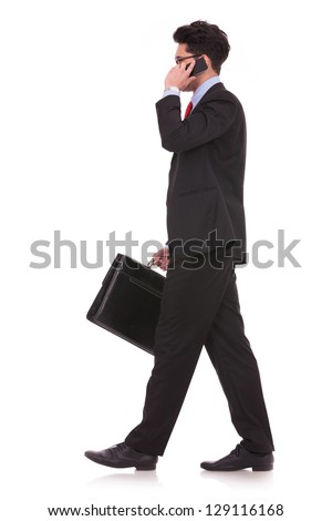side view full length picture of a young business man  walking forward with a briefcase in one of his hands and talking at the phone while looking away from the cameraon white background - stock photo