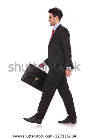 side view full length picture of a young business man walking forward with a briefcase in one of his hands and looking away from the camera on white background - stock photo