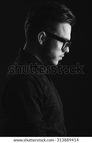 Side view image of a young handsome man with beard, wearing on black shirt and glasses, on dark studio background, close up