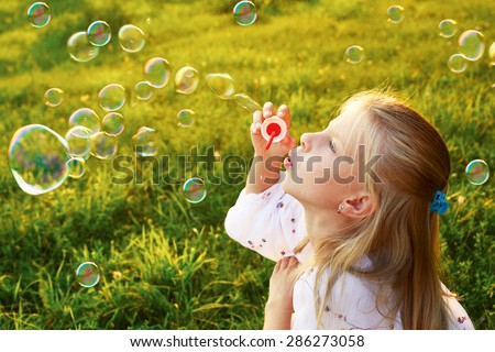 Side view. little girl is blowing a soap bubbles