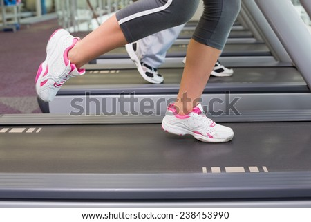Side view low section of a fit couple running on treadmills at the gym - stock photo
