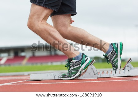 Side view low section of a young man ready to race on running track - stock photo