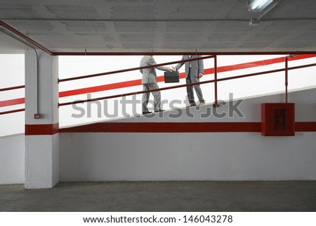 Side view lowsection of two businessmen exchanging briefcase on ramp in parking garage - stock photo