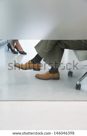 Side view lowsection of two office workers sitting in office - stock photo