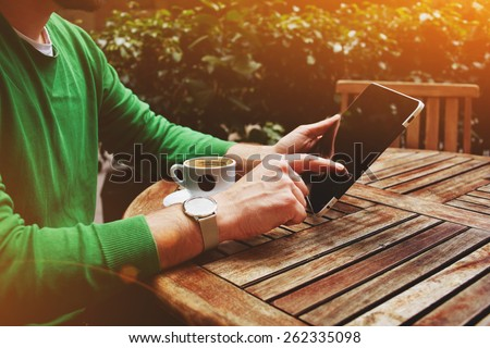 Side view male freelancer sitting on the terrace with cup of coffee and touch screen tablet while having a break, man's hands typing message on digital tablet sitting at cafe table with plants, flare - stock photo
