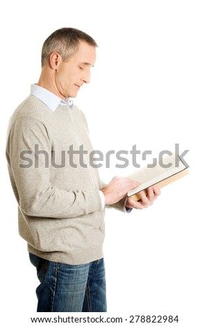 Side view mature man reading a book.
