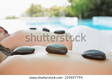 Side view mid section of a couple enjoying stone massage at health farm - stock photo