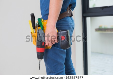 Side view mid section of a handyman with drill and tool belt by the wall