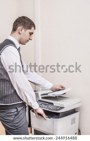 Side view midsection Portrait of young adult businessman using photocopy machine in office Business man white collar holding paper document against texture wallpaper background Empty space  - stock photo