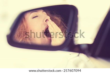 Side view mirror view reflection sleepy tired fatigued yawning exhausted young woman driving her car in traffic after long hour. Transportation sleep deprivation accident concept - stock photo