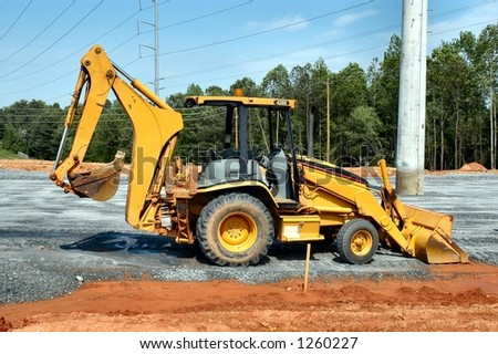 Side view of a backhoe loader at rest - stock photo