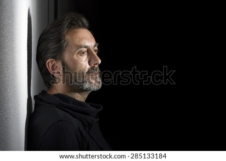 Side view of a bearded man with a black shirt and looking at the distance in a black background - stock photo