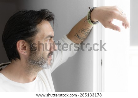 Side view of a bearded man with a white shirt and looking through a window in a shiny day - stock photo
