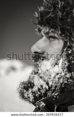 Side view of a bearded young man with hat in winter season.Monochrome