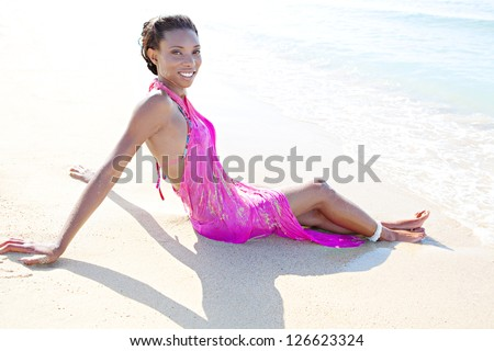 Side view of a beautiful black woman sunbathing in a beach shore, wearing a bright pink sarong with her feet in the water, on vacation. - stock photo